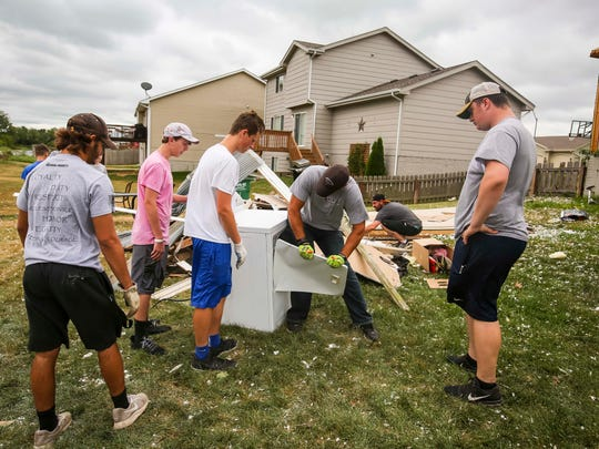 Members of the Bondurant-Farrar football team help cleanup debris on the west end of Bondurant, Iowa, Friday, July 20, 2018, after a tornado slashed through the town the day Thursday afternoon.