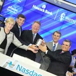 Hancock Holding Company executives opened The Nasdaq Stock Market recently to honor the strong spirit of people and places affected by Hurricane Katrina. Pictured (from left) are Investor Relations Manager Trisha Carlson, Chief Operating Officer Shane Loper, President & CEO John Hairston, Chief Financial Officer Mike Achary, and Whitney Bank President Joe Exnicios.