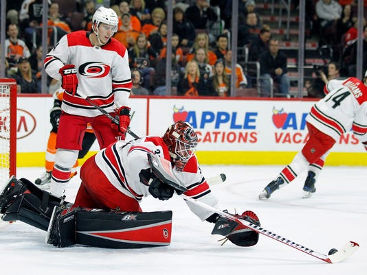 Carolina Hurricanes goalie Scott Darling reaches out to cover the puck while Haydn Fleury, rear, looks on during the second period of an NHL hockey game against the Philadelphia Flyers, Thursday, April 5, 2018, in Philadelphia, PA. (AP Photo/Tom Mihalek)