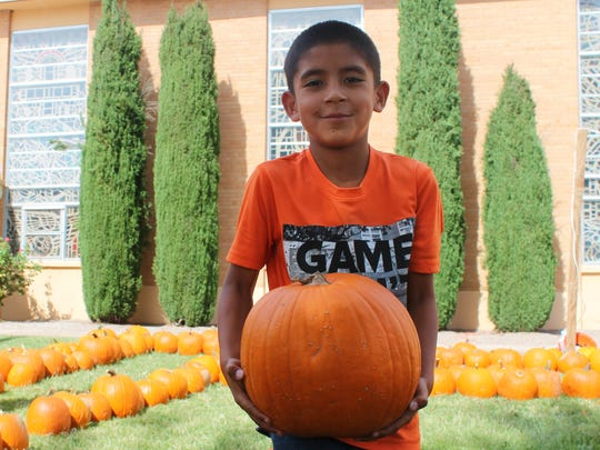 Dadrian Lechuga, 7 years old, holds his selection from the Grace United Methodist Pumpkin Patch.