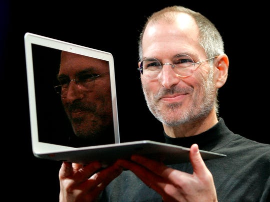 Apple CEO Steve Jobs holds up the new MacBook Air after