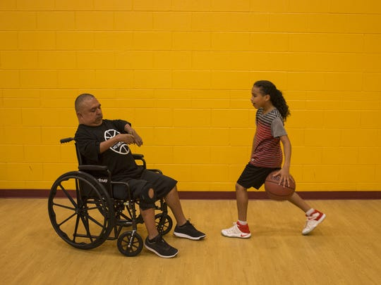 David Solano, left, videos Devareon Watson during Solano's No Limit Hoops in February.