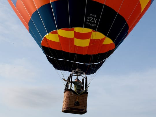 Zee-Nith balloon pilot Alex Jonard II, of Illinois, waves to his ground crew as he takes off during the 2018 Coshocton Hot Air Balloon Festival's opening day on Thursday, June 7, 2018 at the Coshocton County Fairgrounds. Jonard, who grew up in West  Lafayette, returned home to participate in the annual event.