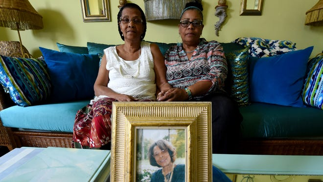Jennie Settles, left, and Gladys Mosley pose in Mosley's York home near a photograph of their sister Hattie Dickson on Tuesday. Dickson, who was a central figure in the 1969 riot trials, passed away on Monday.