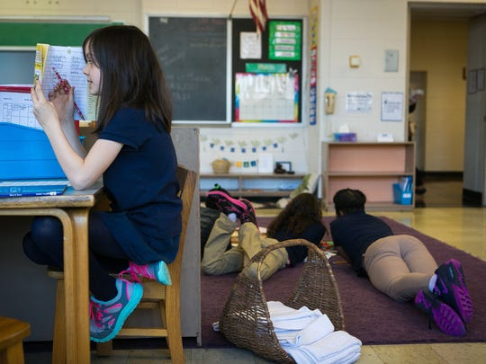 Second-grader Maya Staab works on her reading skills at the Montessori Academy at Christina.