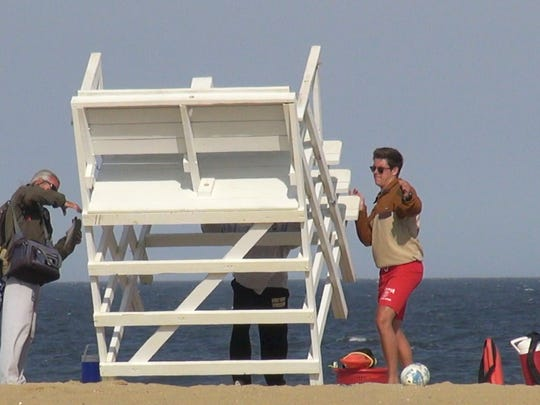 Lifeguards drop down their lifeguard stand as they go offduty at the end of their shift on a week day.