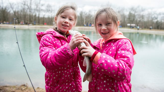 Twins Ashlyn and Keira Peake, 6, hold up one of the trouts they caught while fishing at Kaiser Lake in New Oxford during the first day of trout season on Saturday.