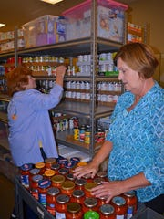 Volunteers representing First Baptist Church of Madison, Kay Gilbert, left and Nancy Hopping, right, both of Canton, help restock shelves with canned food items while spending time working at the MADCAP food pantry located in Canton.
