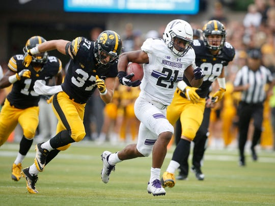 Northwestern junior running back Justin Jackson outruns Iowa safety Brandon Snyder en route to a touchdown on Saturday, Oct. 1, 2016, at Kinnick Stadium in Iowa City.
