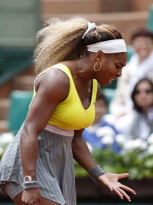 Serena Williams of the U.S. gestures after missing a return during the second round match of the French Open tennis tournament against Spain's Garbine Muguruza at the Roland Garros stadium, in Paris, France, Wednesday, May 28, 2014.