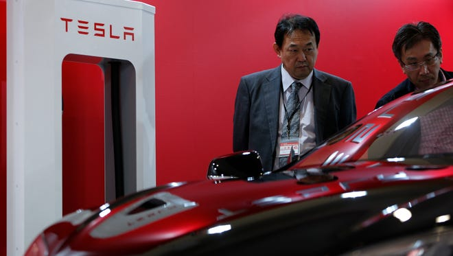 Attendees look at a Tesla Motors Inc. Model S electric vehicle on display at the 43rd Tokyo Motor Show 2013 in Tokyo, Japan, on Thursday, Nov. 21, 2013.