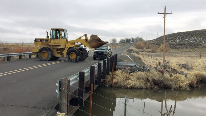 Trucks and a front-end loader block the road to the Malheur Wildlife Refuge at the site of an FBI checkpoint outside of Burns, Ore., Friday, Feb. 12, 2016. The FBI allowed a group of reporters to move nearer to the refuge Friday morning as part of a guided tour. The group was not allowed to enter the refuge, which is now considered a crime scene.(AP Photo/Rebecca Boone)