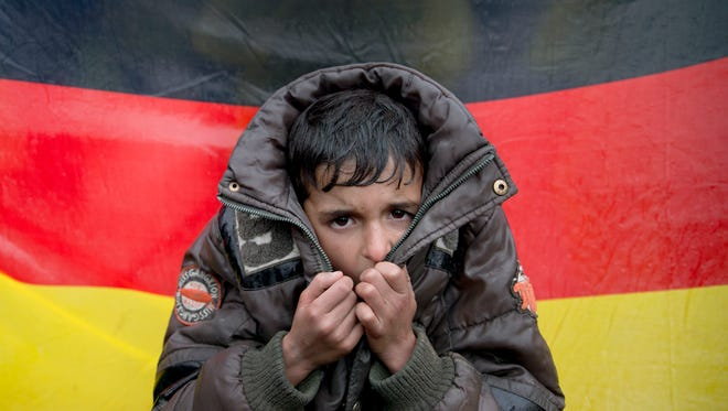 A child tries to warm his hands, backdropped by Germany's flag as protesting migrants stage a sit-in on the railway tracks at the northern Greek border station of Idomeni on March 9, 2016.