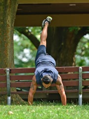 Frankie Serrano, a PURSUIT coach, uses a bench to do pushups on Wednesday, August 3, 2016 at Chambersburg Memorial Park. The new concept takes fitness out of the gym and into the outdoors where participants find obstacles to overcome and jog to various locations.
