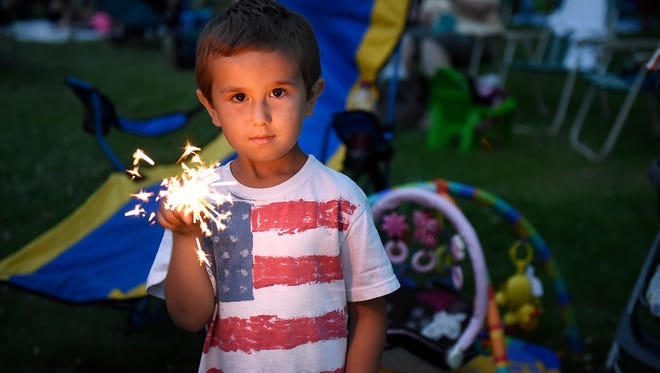 Jacob Coghlin holds a sparkler while waiting for the fireworks to begin at Hester Park in St. Cloud in 2015.