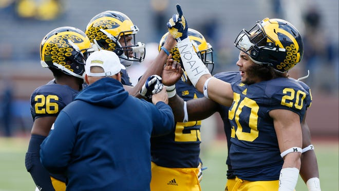 Michigan defensive backs high-five while warming up for a game against Rutgers on Saturday, Nov. 7, 2015, in Ann Arbor.