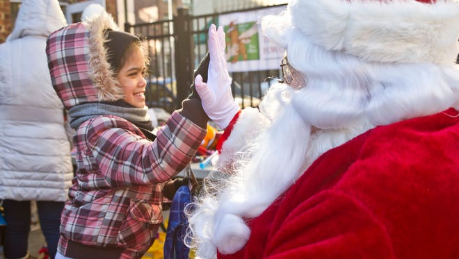 Laylanni Caldeira, 8, of Asbury Park greets Santa at the event. The Asbury Park Toy Drive takes over a vacant storefront in downtown Asbury Park as hundreds of people line up for gifts, clothing, and food.Asbury Park, NJSaturday, December 19, 2015@dhoodhood