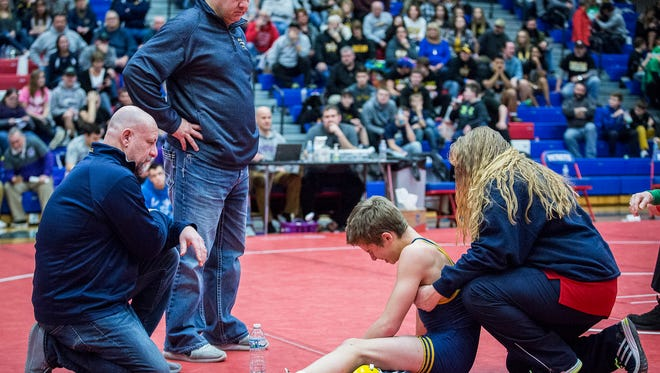FILE -- Delta's Gary Schliessman (bottom left) looks over one of his wrestlers during the regional at Jay County High School Saturday, Feb. 4, 2017. Schliessman resigned as the Eagles' head coach after six years in the position.