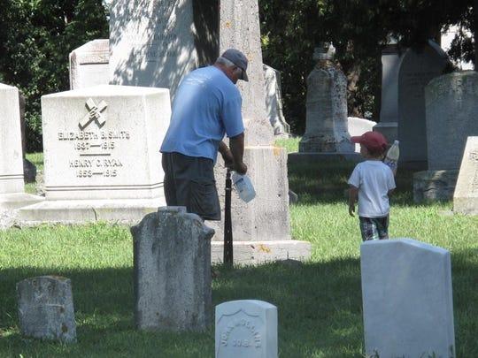 Jim Woodman and Henry, grandson of Deborah Hardy, clean a gravestone on Aug. 20 at St. Joseph's Cemetery in Burlington.