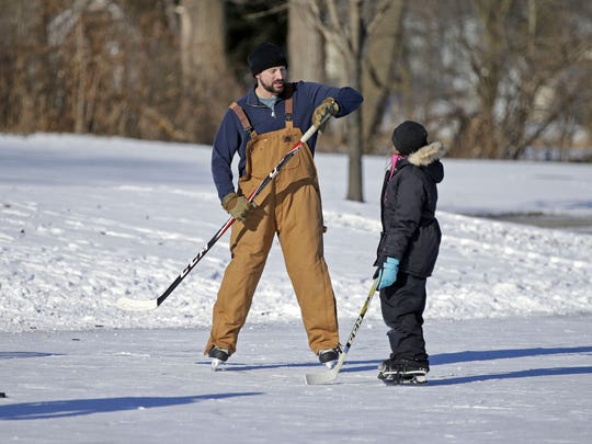 Andrew Jansen of Neenah talks with his daughter, Ally, on the ice at Washington Park in Neenah.