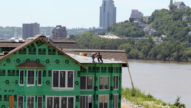 Against the backdrop of Mt. Adams, roofers work on one of the homes in the Manhattan Harbour development along the Dayton riverfront.