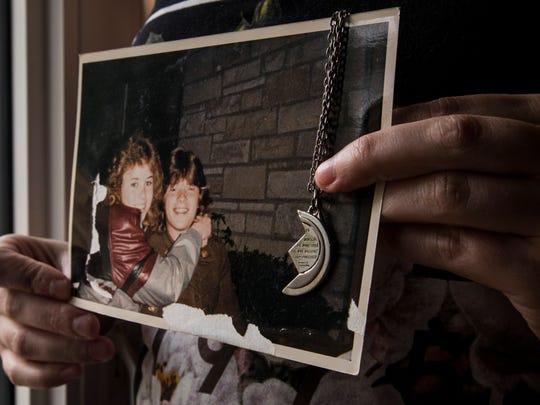 Amanda Cottrell holds a photo of her mom, Kathleen Reuteler, and her dad, Brian Sullivan, from when they were dating in the 1980s. When Brian died in a car crash in 1988, he was unaware that Kathleen was pregnant with Amanda. The necklace was a gift from Kathleen to Brian. The left half is in his coffin, and Amanda now treasures the other half. It is inscribed with a verse from Genesis about God watching over the couple when they were apart.