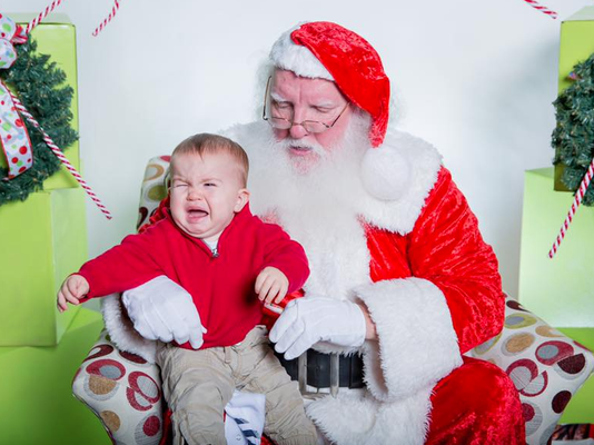 baby crying sitting on santa claus' lap