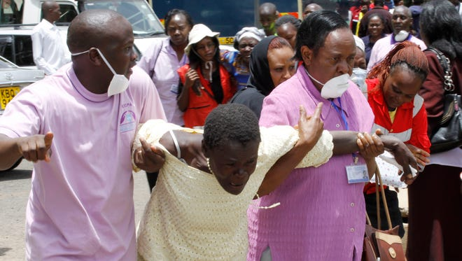 Medical staff console a woman after she  viewed the body of a relative killed in Thursday's attack at Garissa university in northeastern Kenya, at the Chiromo funeral home in Nairobi, Kenya,