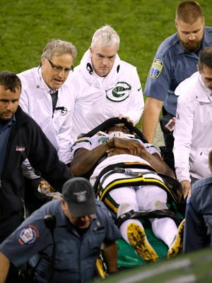Sep 28, 2017; Green Bay, WI, USA; Teammates gather around Green Bay Packers wide receiver Davante Adams (17) as he is taken from the field on a stretcher after being drilled by Chicago Bears inside linebacker Danny Trevathan (not pictured) during the third  quarter at Lambeau Field.