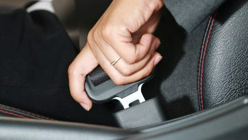 Business woman hand fastening a seat belt.