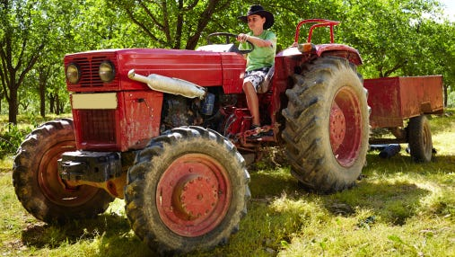Teenage boy driving the tractor