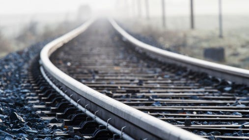 A woman climbed out of her car moments before an oncoming train destroyed the vehicle, which had become stuck on railroad tracks near Lake Lansing early this morning, police said.