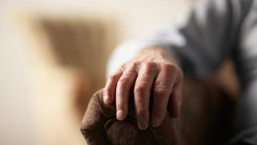 Senior man resting hand on side of armchair