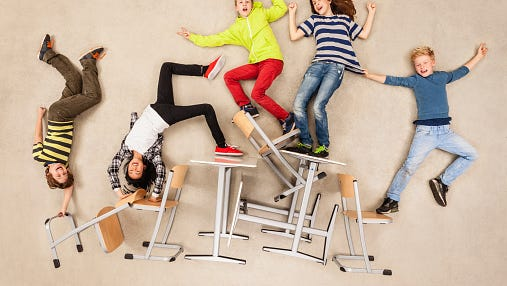 Children balancing on school chairs.