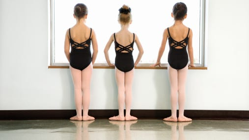 Rear view of dance students standing by window.
