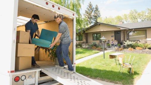 Men unloading chair from moving van