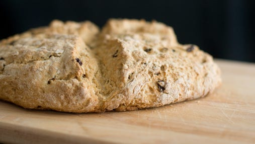 A loaf of Irish soda bread with dried fruit.