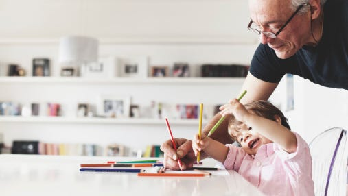 Grandfather help his grandson with drawing