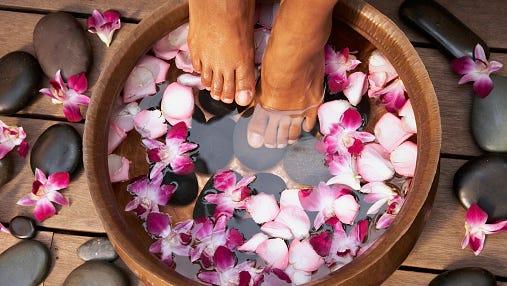 Close up of feet of Black woman soaking in bath
