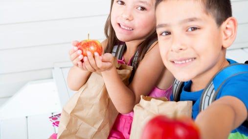 Siblings eating school lunch