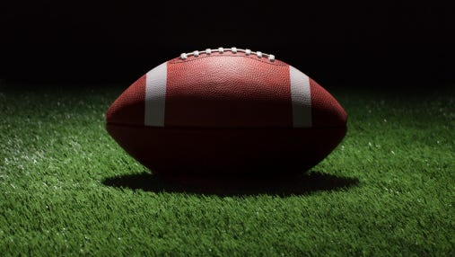 Football on grass field at night with spot lighting