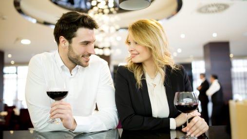 A couple meet and mingle at a bar.