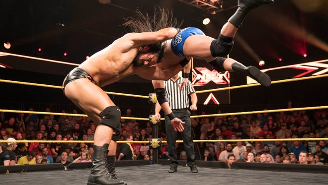 Drew McIntyre, left, delivers a move to Roderick Strong.