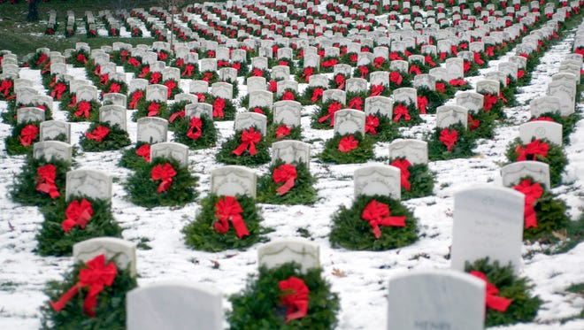Christmas wreaths adorn head stones at Arlington National Cemetery.