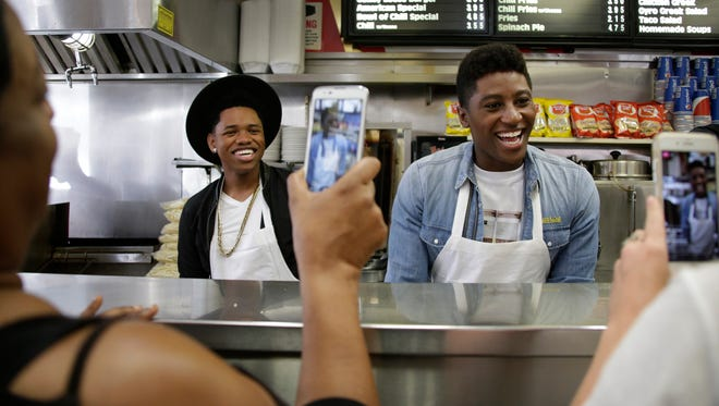 Cast members from the movie 'Detroit' Nathan Davis Jr. ( who plays Aubrey), left, and Joseph David-Jones, (Morris), have their photos taken as they help to hand out 316 free coney dogs from American Coney Island for DetroitÕs 316th birthday coney dog giveaway in Detroit Monday July 24, 2017. 'Detroit', the drama from Oscar-winning director Kathryn Bigelow, will have its world premiere at the Fox Theatre in Detroit on Tuesday. It opens at theaters in limited release July 28 and at 2,000-plus theaters August 4. Mandi Wright/Detroit Free Press