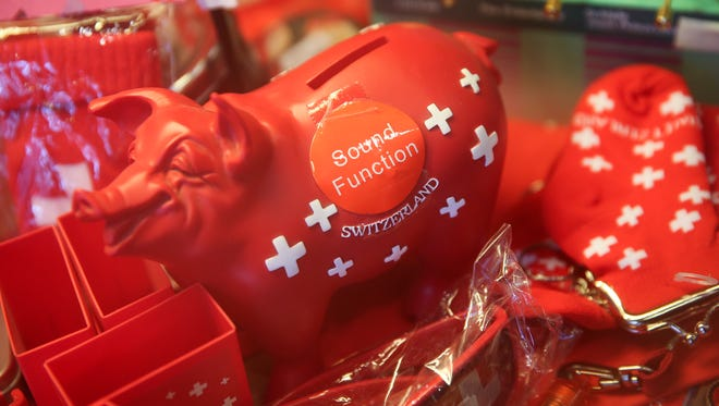 "A red ""piggy bank"" branded with the Swiss national emblem sits for sale in a souvenir shop in Davos, Switzerland, on Jan. 17."