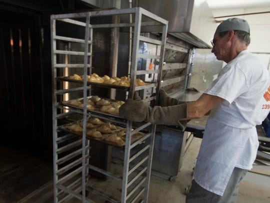 Todd Johnson, the owner of the Artisan Bread Co., pulls cheese danishes from one of his ovens at his Fowler Street establishment Tuesday, the official opening day of the business.