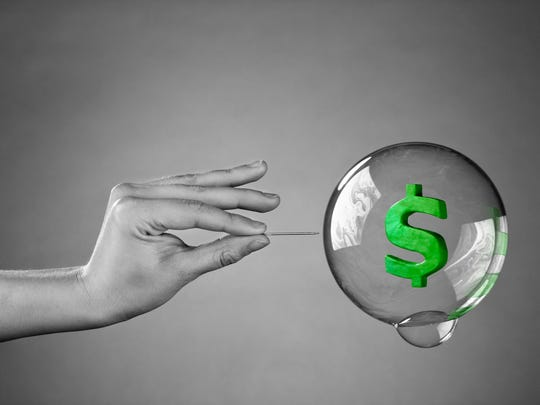 A hand with a needle popping a bubble with a dollar sign inside it.
