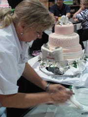 Donna Barley working on a wedding cake on day two of the IDDBA Cake Decorating Competition in Atlanta.