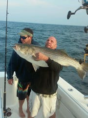 Chris Popo holds a 46-pound striped bass caught May 19 on the Tin Knocker with Captain John Pellegrino.